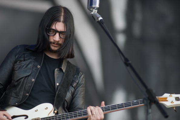 GLASTONBURY, ENGLAND - JUNE 26:  Jack Lawrence from 'The Dead Weather' performs live on the Pyramid Stage during Day 3 of the Glastonbury Festival on June 26, 2010 in Glastonbury, England. This year sees the 40th anniversary of the festival which was started by a dairy farmer, Michael Evis in 1970 and has grown into the largest music festival in Europe.  (Photo by Ian Gavan/Getty Images)