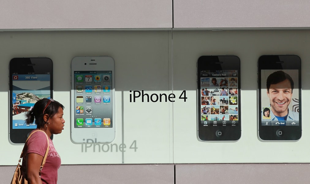 SAN FRANCISCO, CA - OCTOBER 14:  A pedestrian walks by a display of the new Apple iPhone 4Gs at an Apple Store on October 14, 2011 in San Francisco, United States.  The new iPhone 4Gs went on sale today and features a faster dual-core A5 chip, an 8MP camera that shoots 1080p HD video, and a voice assistant program.  (Photo by Justin Sullivan/Getty Images)